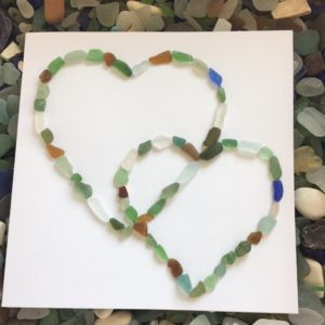 Handmade card decorated with two heart shapes made with light green seaglass